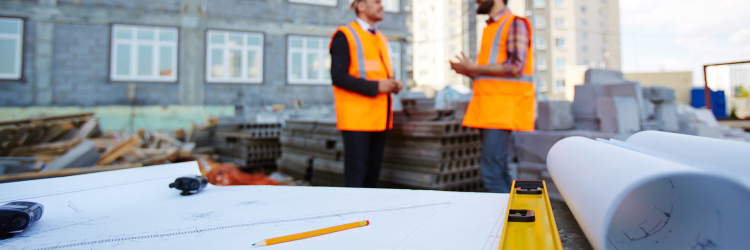 blueprint in front of two engineers at a construction site (source: freepik.com)