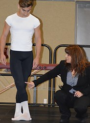 Using her son, Matthew Herman (left), as her model, Rebecca Fishman, DO, points out potential problem areas for ballet dancers.