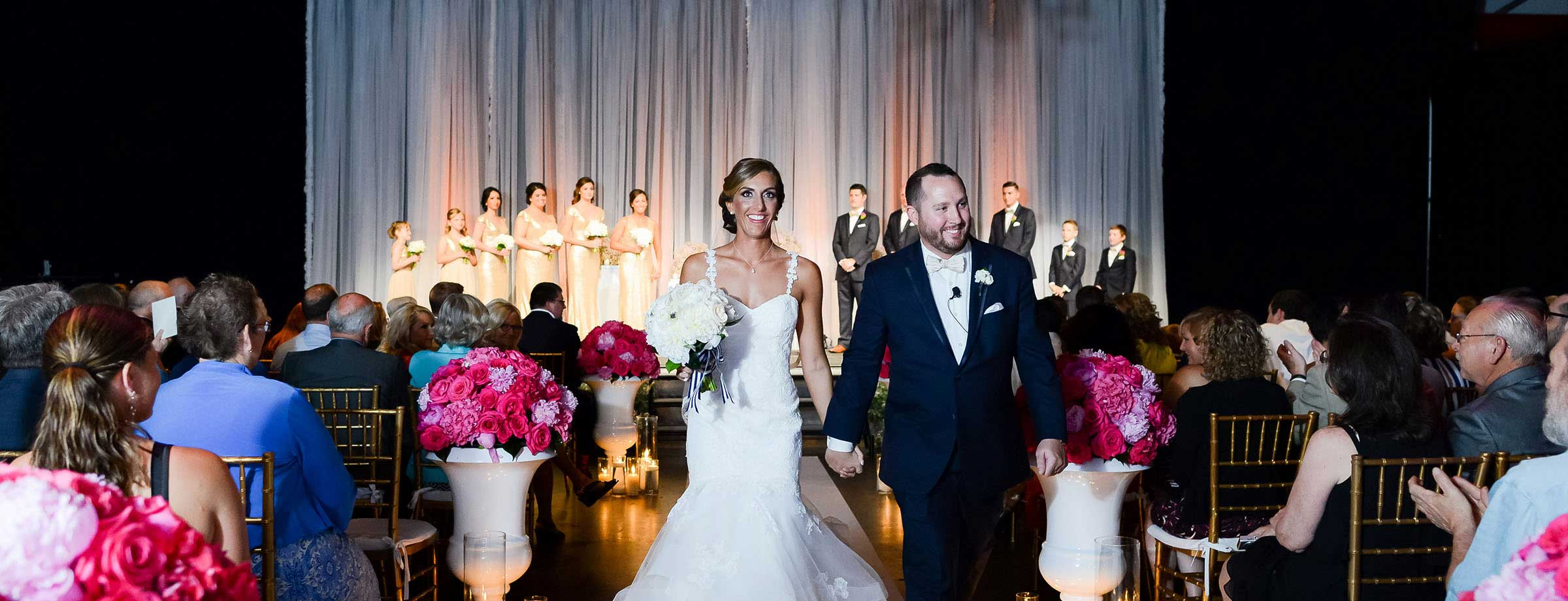 Mr. and Mrs. walking down the aisle at The Crane Bay in Indianapolis Indiana