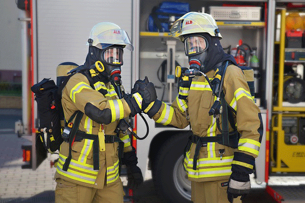Firefighters shaking hands in front of firetruck