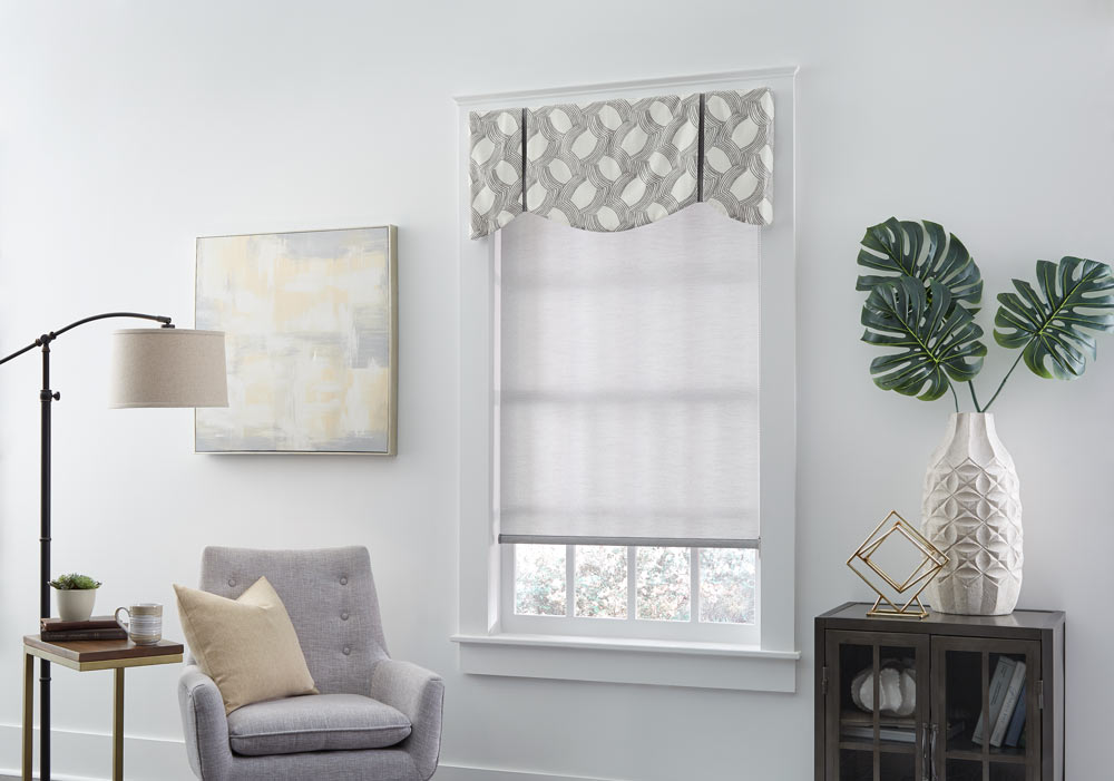 gray Genesis® Roller Shade with an Interior Masterpieces® gray and white patterned fabric valance next to a light gray chair with a tan pillow on it