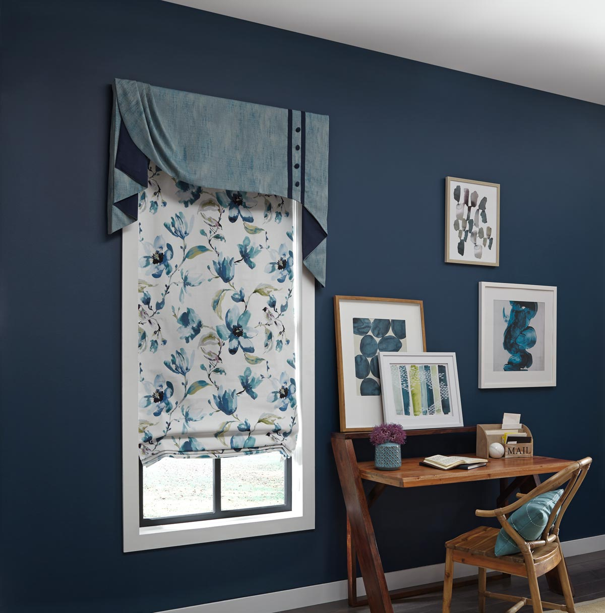 Window in a blue wall with an Interior Masterpieces® custom fabric cornice and a roman shade next to a wooden table with paintings hung behind it
