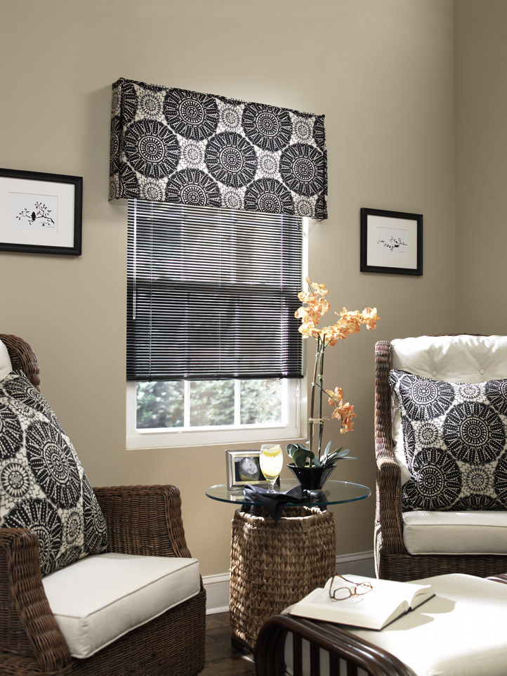Dark Classic Collection® Aluminum Blinds against tan walls with an Interior Masterpeices® Fabric Cornice with a dark and light geometric pattern and Custom Pillows on brown and white chairs