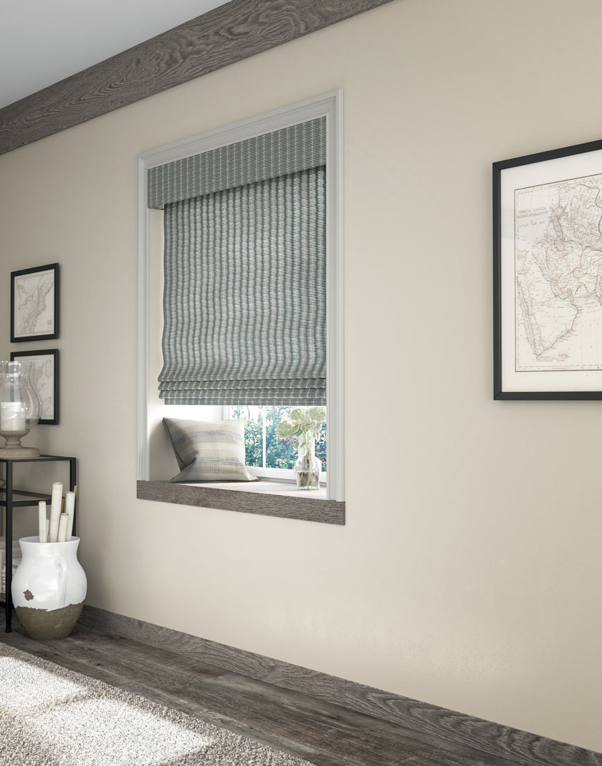 a white and blue Manh Truc® Woven Wood Shade against a tan wall with gray wood floors and window bottom