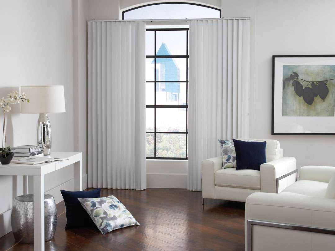 White Sheer Visions® Vertical Blinds hanging in a window in a room with wood floors and white furniture around and custom Interior Masterpieces® pillows