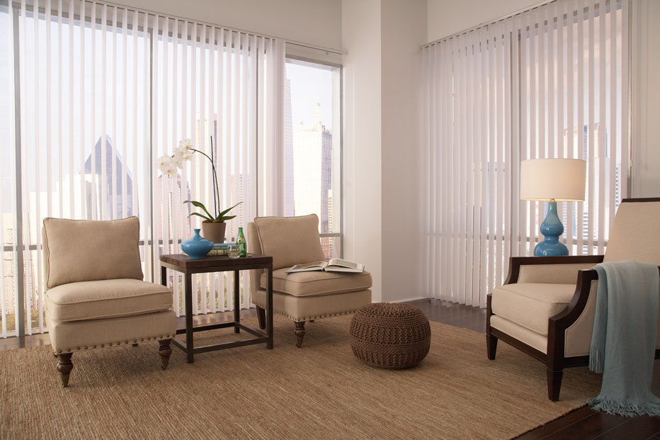 Two large picture windows with Discoveries® Vertical Blinds hanging in them in the open position in a room with tan furniture and blue accent pieces