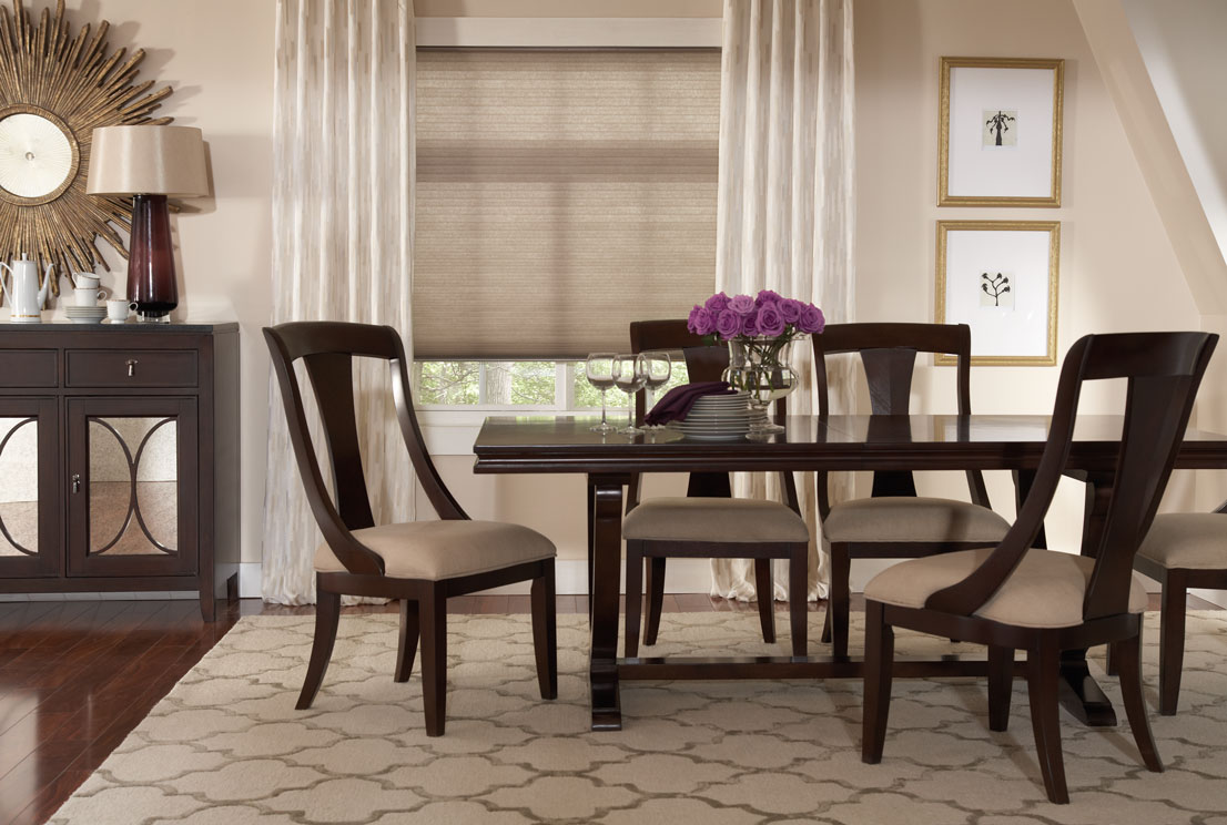Lightly colored tan Parasol® Continuum Cord Loop Shades with Custom Interior Masterpieces® Draperies in a dining room with dark wood chairs and table
