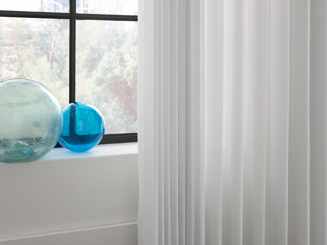 Close up of white Sheer Visions® Vertical Blinds with some blue glass decorations in a window