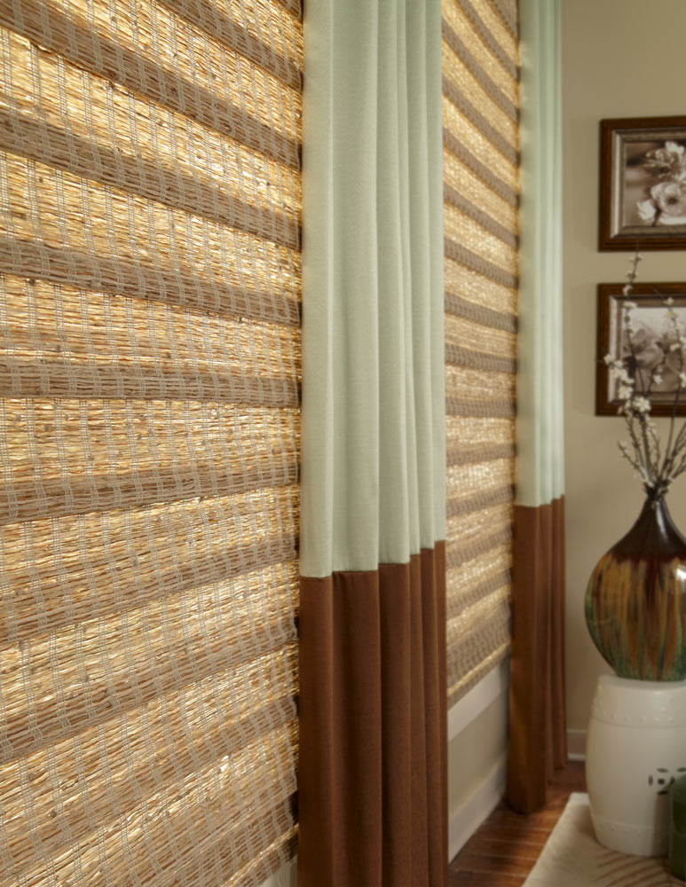 close up of light brown and dark brown Manh Truc® Woven Wood Shades and light green and dark brown Interior Masterpieces® Draperies