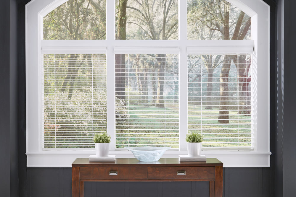 "three white Heartland Woods® Wood Blinds in 1"", 2"" and 2 1/2"" slat sizes in the open position behind a brown desk against dark gray walls"