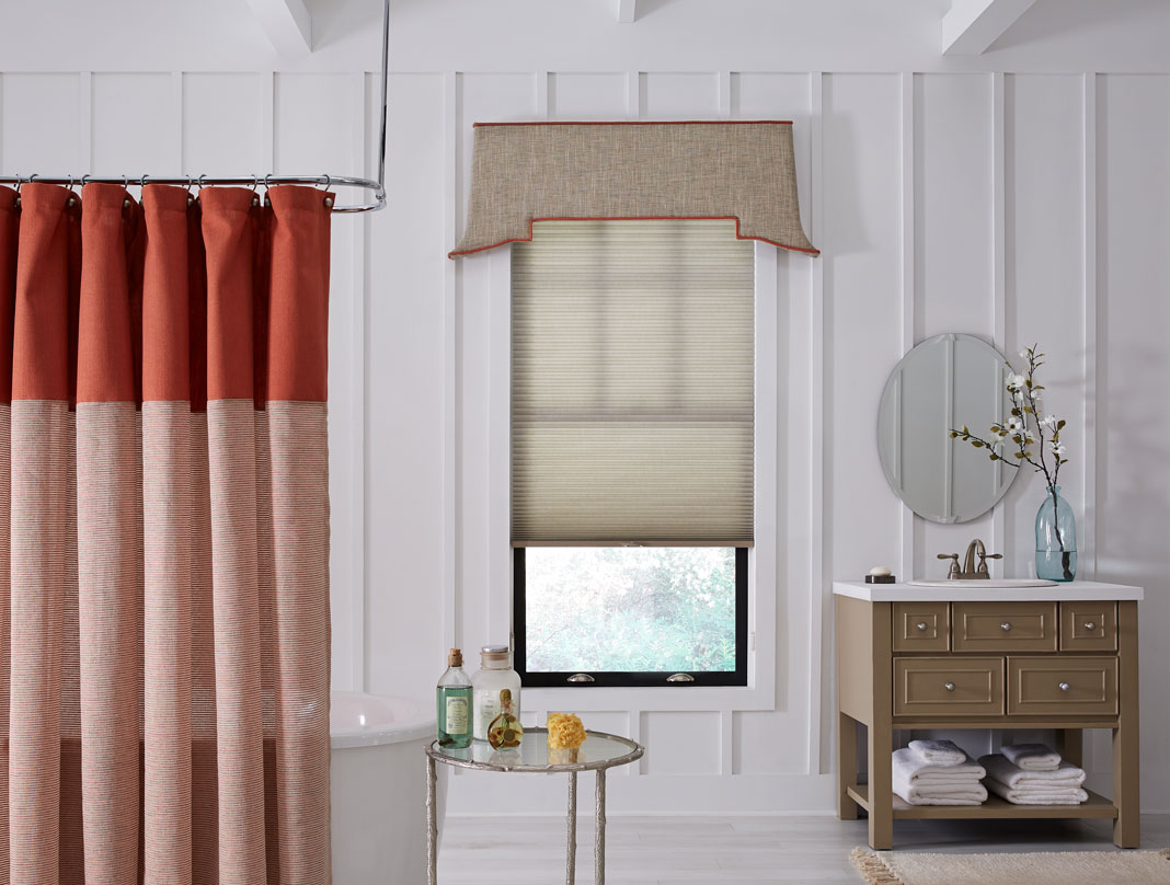 tan Parasol® Cellular Shades & Interior Masterpieces® Fabric Cornice with red trim in a bathroom with a red shower curtain and brown vanity