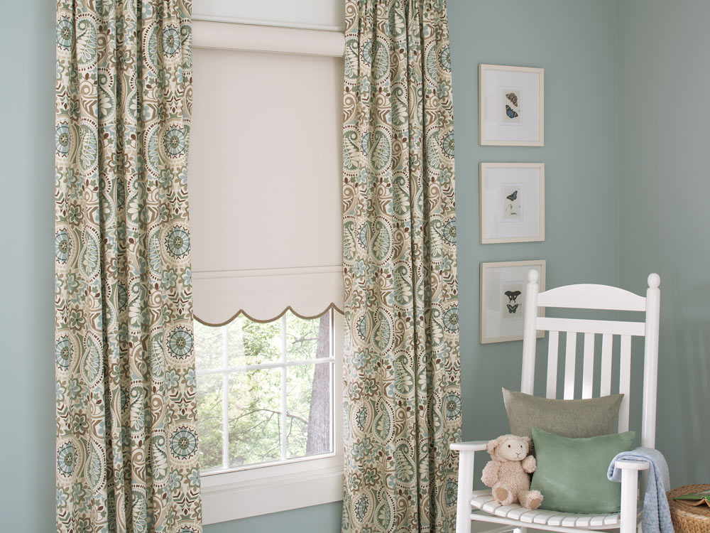 light tan Genesis® Roller Shade with Scalloped Hem, brown Decorative Trim & Interior Masterpieces® Draperies in a floral pattern against blue walls