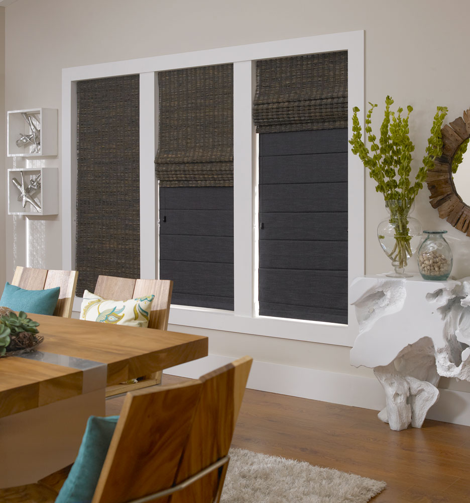 Three dark Manh Truc® Duo-Fold Woven Wood Shades in different raised positions showing the room darkening liner behind the Woven Wood Shade