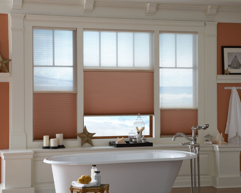 3 red and tan Parasol® Duo-Lucent Cellular Shades in a large bathroom picture window behind a large white stand alone bath tub
