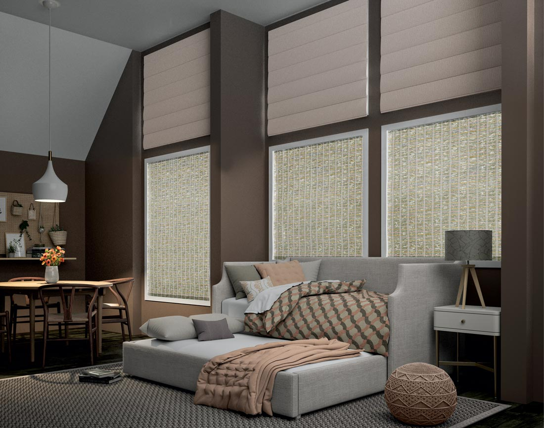 Light tan Interior Masterpieces® Motorized Roman Shades in three windows high near the ceiling above 3 windows with Manh Truc® Motorized Woven Wood Shades behind a couch and sleeper with Interior Masterpieces® Custom Blankets, Pillows and Throws