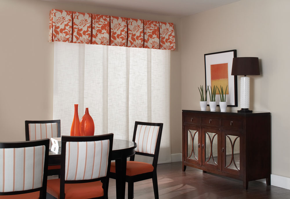 White Genesis® Panel Track system in a large window in a dining room with an Interior Masterpieces® ornage and white fabric wrapped cornice with a black table and orange decorations on it