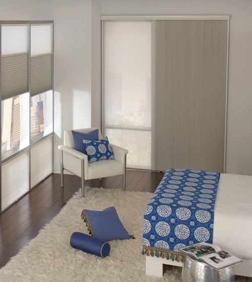 Two toned cellular shades hang horizontally in two windows and vertically on a large window for easy sliding in a high-rise bedroom featuring custom blue medallion patterned bedding.