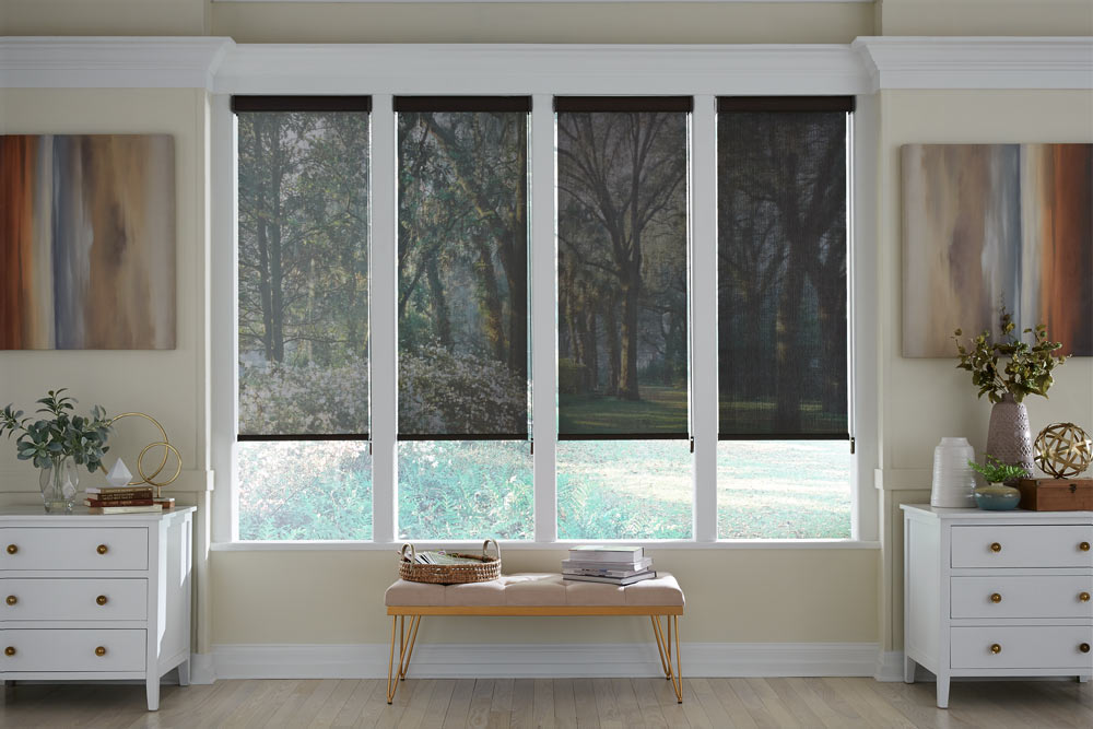 four black Genesis® Cassette Roller Shades showing different opacity levels with the lightest on the left and darkest on the right