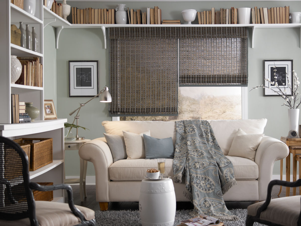 wide dark colored Manh Truc® Woven Wood Shades with dark blue Custom Banding behind a cream colored couch with blue, tan and gray custom pillows and a light blue throw
