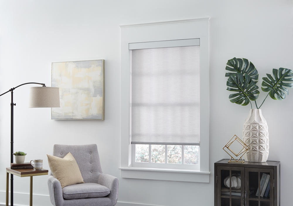 gray Genesis® Roller Shade next to a light gray chair with a tan pillow on it