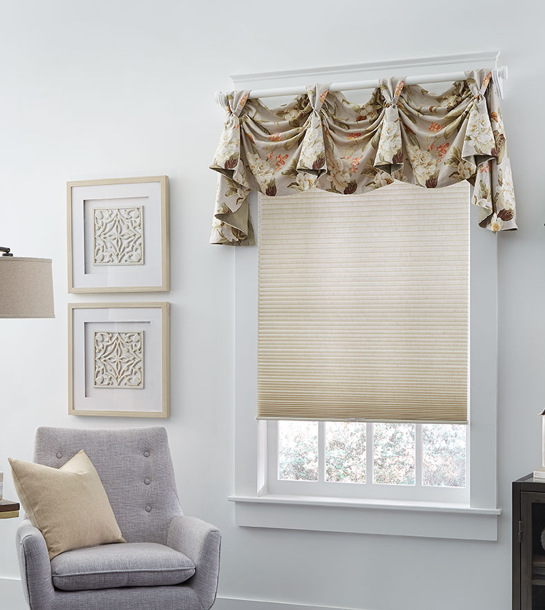 A light taupe cellular shade hangs in the window of a seating area featuring a modern light gray chair, and a floral fabric swag pole valance.