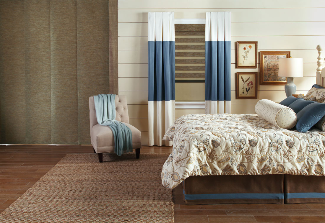 Genesis® Panel Track system with Allure® companion transitional shade in a bedroom with Interior Masterpieces® draperies and custom bedding
