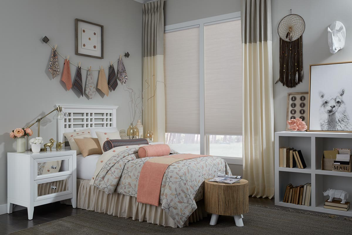 Custom Interior Masterpieces® Stationary Draperies hung in a window with a fabric shade in front of a bed that has custom bedding and accessories