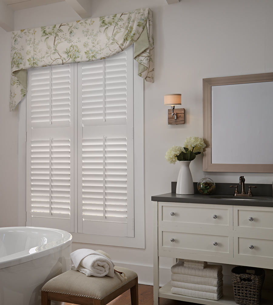 white Parke® Shutter with a tan and yellow floral patterened Interior Masterpieces® Fabric Valance in a bathroom with beige walls and a white stand alone tub in the foreground