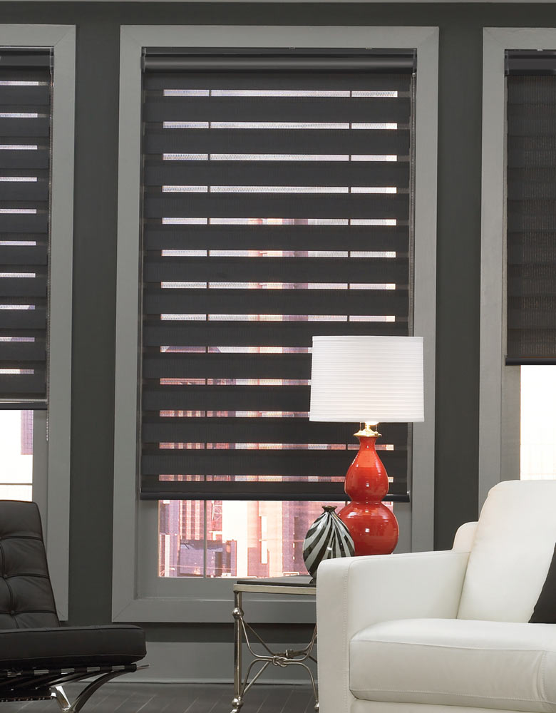 Dark Allure® Transitional Shade against a dark wall with a light gray window fram with a red lamp on a black table and white couch in front