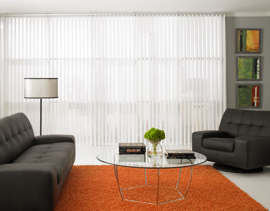 White Sheer Visions® Vertical Blinds hanging in a large window in a room with an orange rug and black furniture