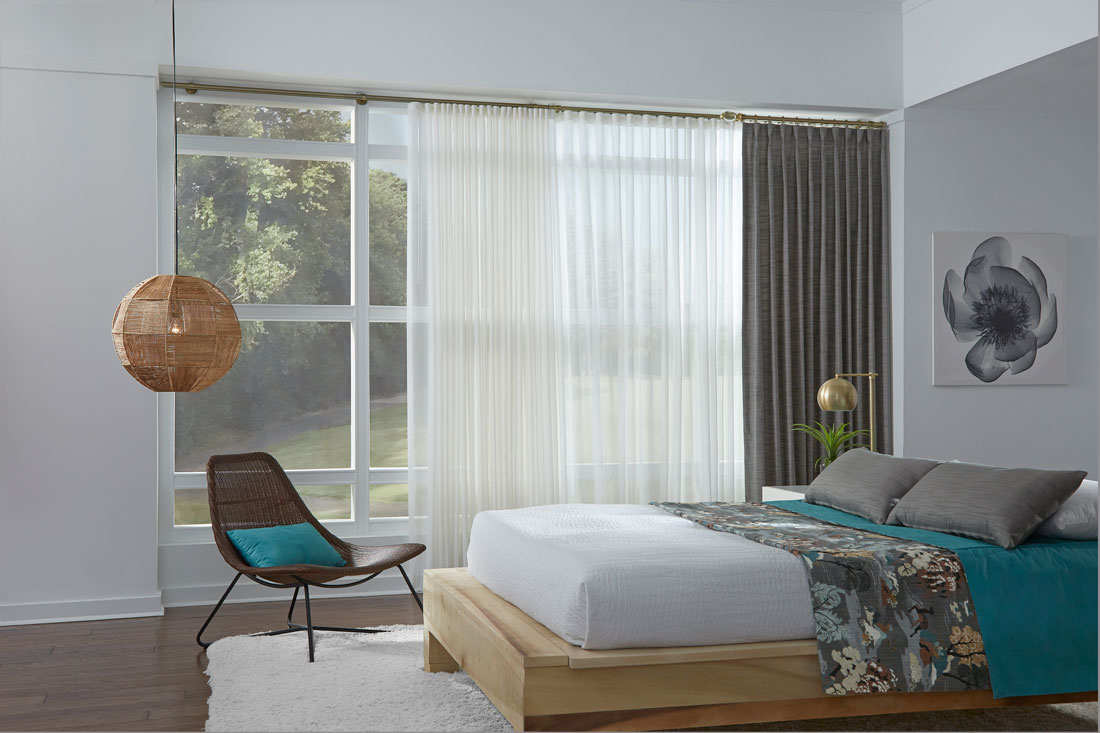 Bedroom scene with a large picture window and a sheer white Interior Masterpieces® Drapery with a Gray Solid stationary panel next to a bed with Custom Interior Masterpieces® Pillows and Blankets in Teal and a Floral pattern