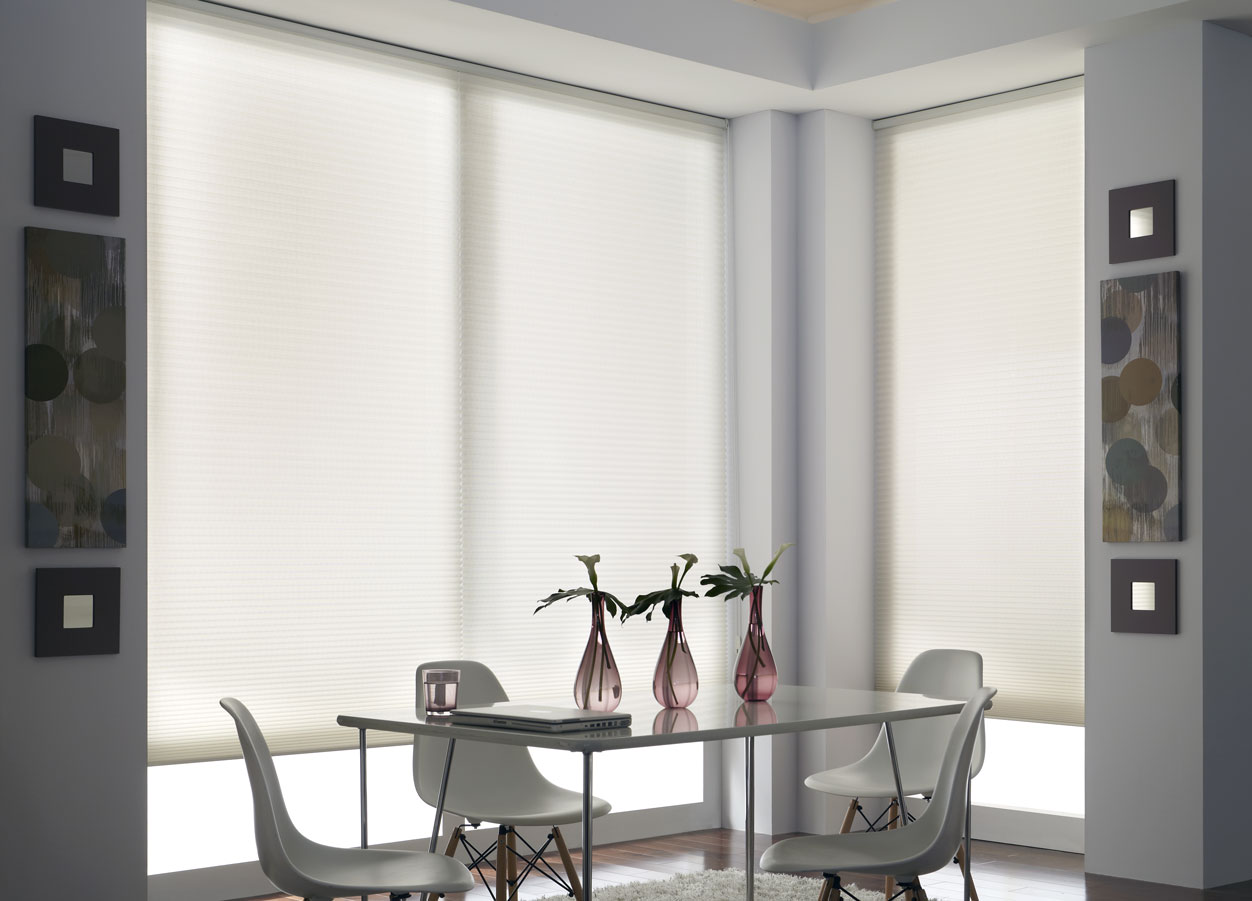 large white Parasol® Cellular Shades surrounding a glass table with gray chairs and pink flower vases