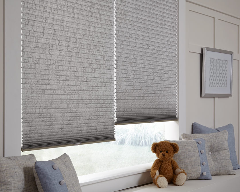 Two child-safe textured gray cellular shades hang in a cozy window nook, with custom throw pillows and a teddy bear on the window bench beneath.
