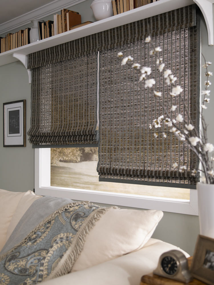 wide dark colored Manh Truc® Woven Wood Shades 2-on-1 with custom banding behing a cream colored couch