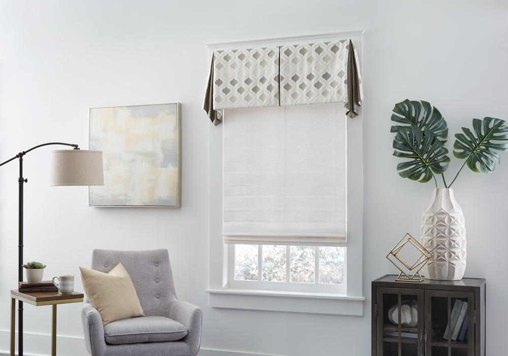 gray Genesis® Roller Shade with Interior Masterpieces® Fabric Valance with a tan diamond pattern next to a light gray chair with a tan pillow on it