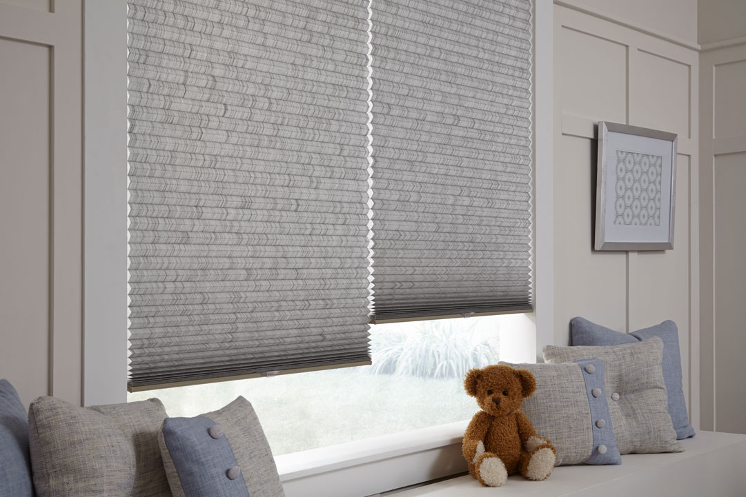 close up view of some gray Parasol® Cellular Shades with matching Interior Masterpieces® Custom Pillows on a bench and a brown teddy bear in between them