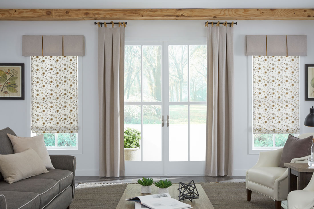 two cream colored floral patterned Interior Masterpieces® Fabric Shades with custom tan Fabric Wrapped valances hanging on each side of a patio door with tan Draperies