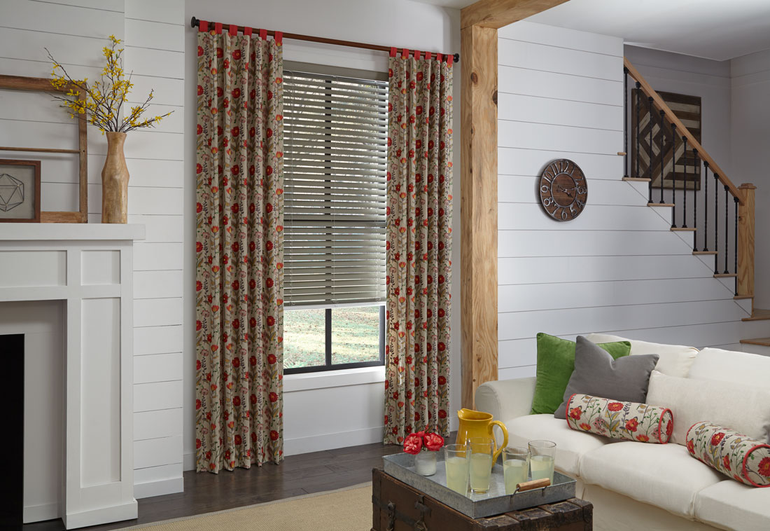 Gray Wonderwood® Wood Blinds with Interior Masterpieces® Draperies in a red floral pattern with Custom Hardware behind a white couch with Custom Pillows