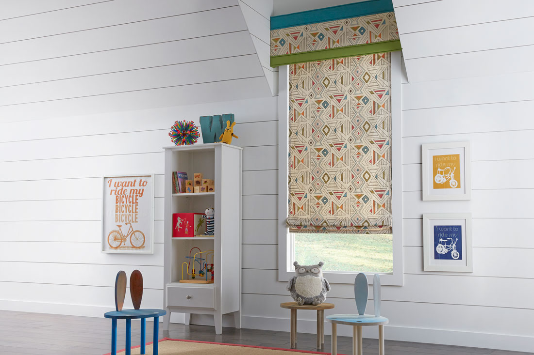 tan Interior Masterpieces® fabric shade with geometric pattern and accenting fabric wrapped cornice in a child's room with small chairs and playthings on shelves
