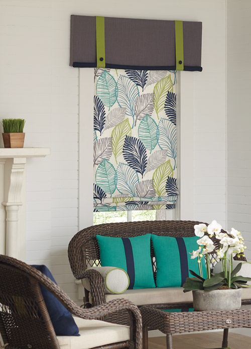 Floral teal, blue, and yellow Interior Masterpieces® fabric shade with gray and green custom cornice behind a chair with teal and blue accenting pillows
