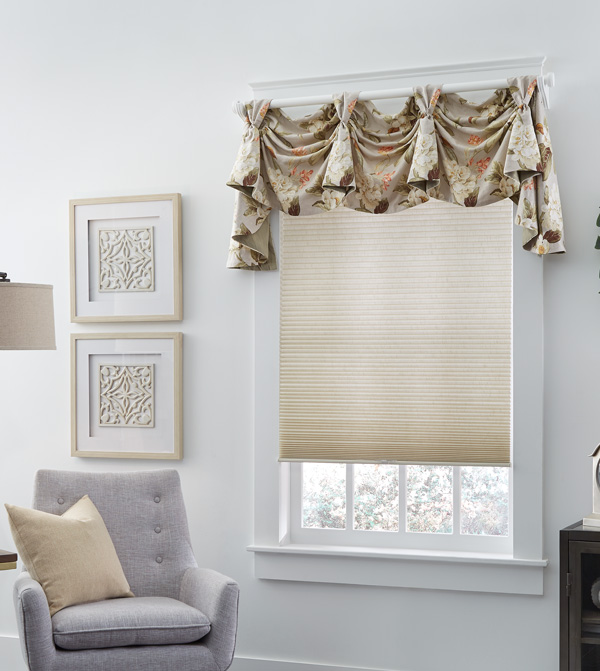 Custom Rod Mounted Interior Masterpieces® valance above a tan cellular shade in a room with white walls and a chair with a custom accent pillow