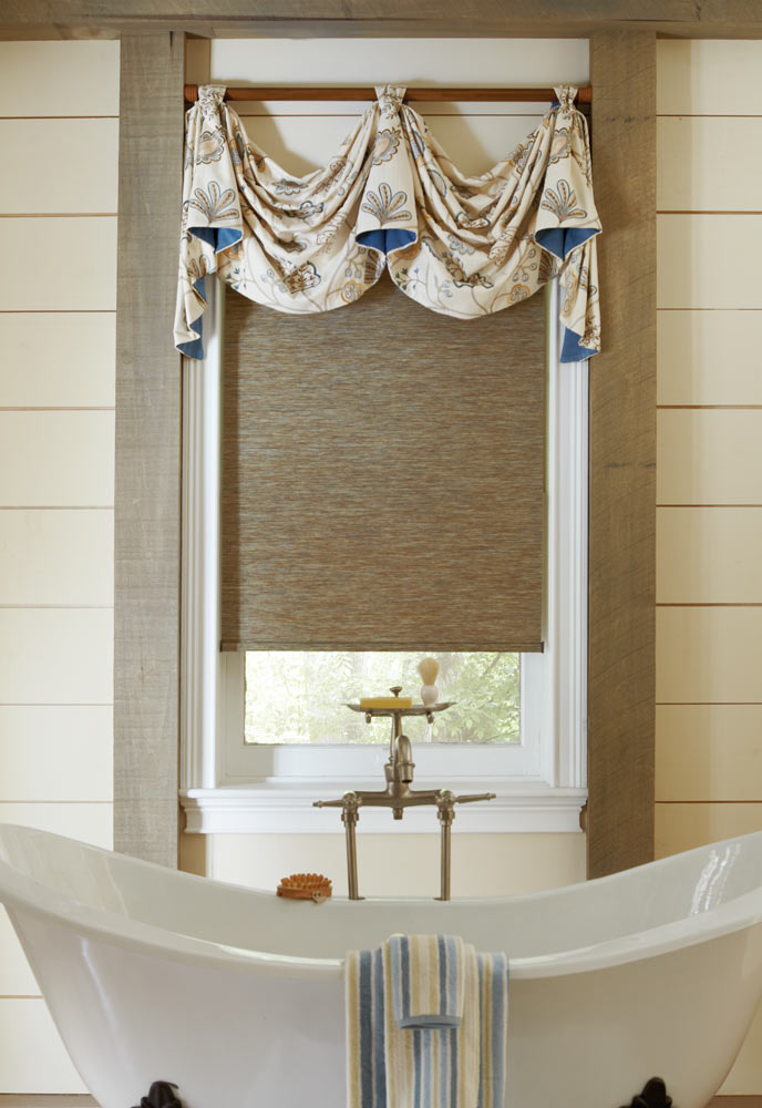 brown Genesis® Custom Roller Shade with a white and blue floral patterned Interior Masterpieces® Fabric Valance behind a white stand alone tub
