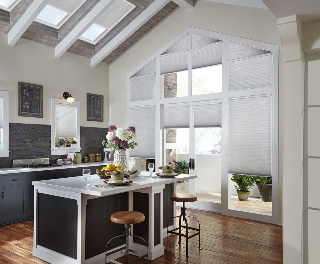Several Parasol® Cellular shades in a large wall of windows that come up to a point that have Palladian Angled specialty shaped Cellular shades at the top along with Parasol® motorized shades in the skylights