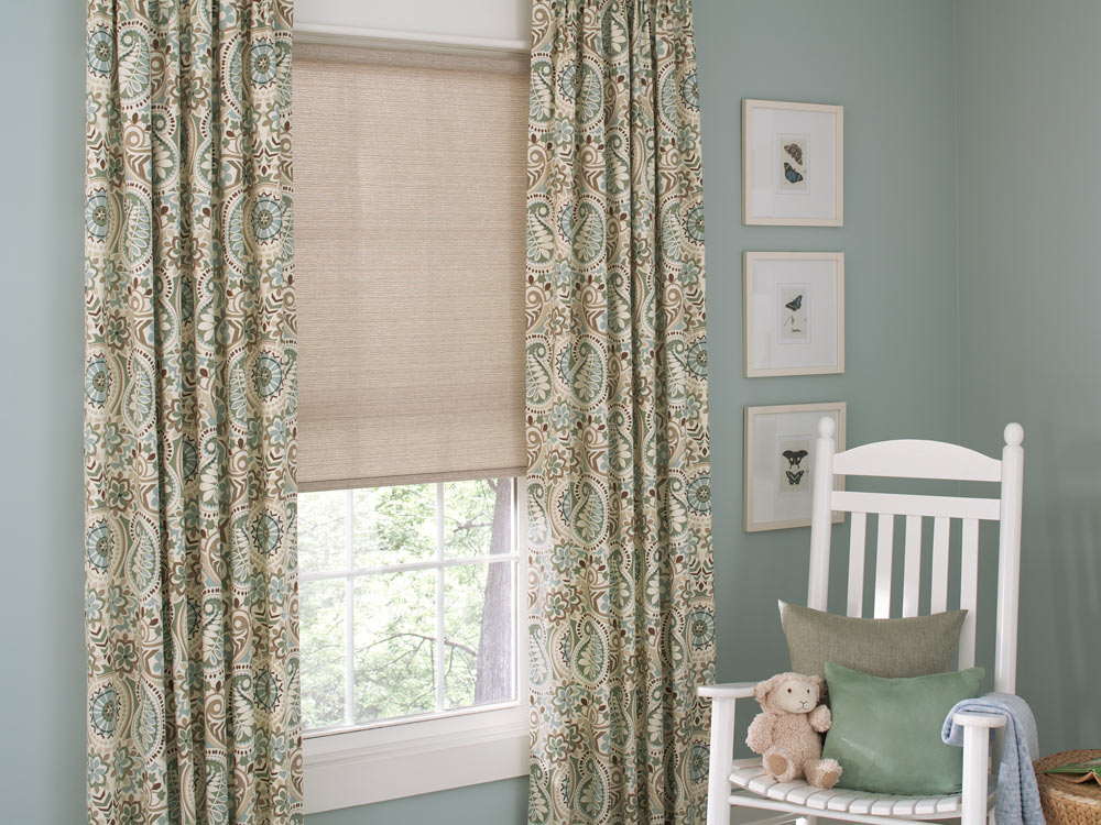 tan Genesis® Roller Shades and floral patterned Interior Masterpieces® Draperies against blue walls with a white chair nearby and a stuffed animal on it