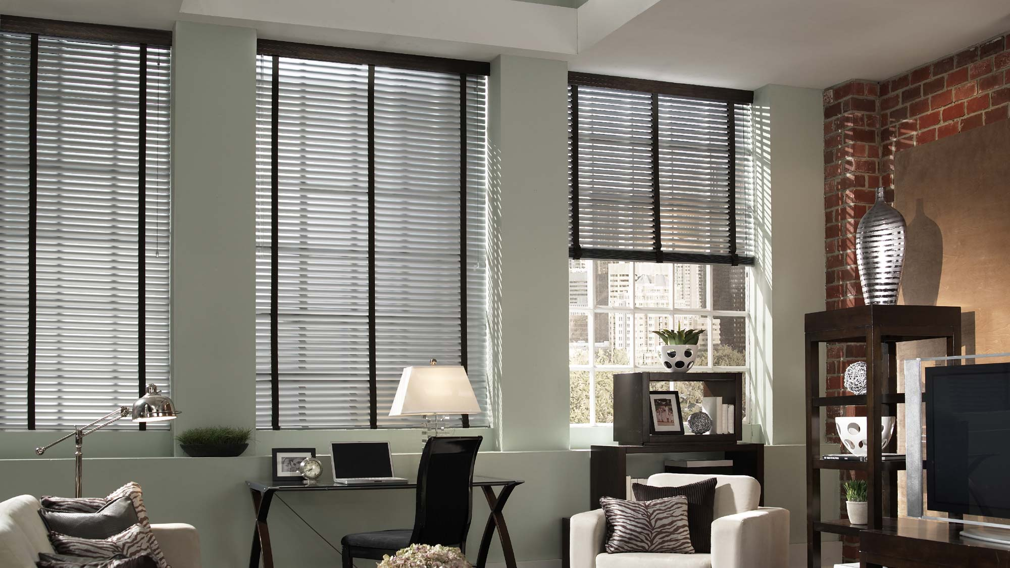 Dark Classic Collection® Aluminum Blinds with Embellishment Trim Banding in an office with a chair that has Interior Masterpieces® Custom Pillows