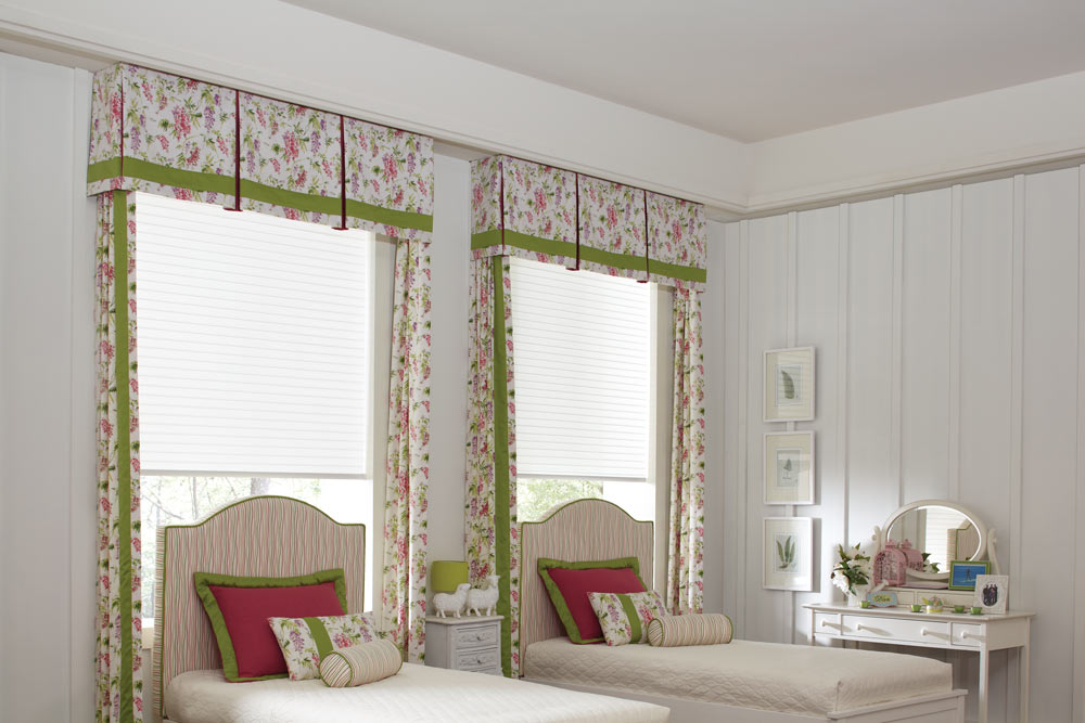 Two white Tenera® Sheer Shades with Interior Masterpieces® Fabric Cornices and Draperies in a floral pink, green, purple, and white pattern with matching Headboard and Custom Bedding