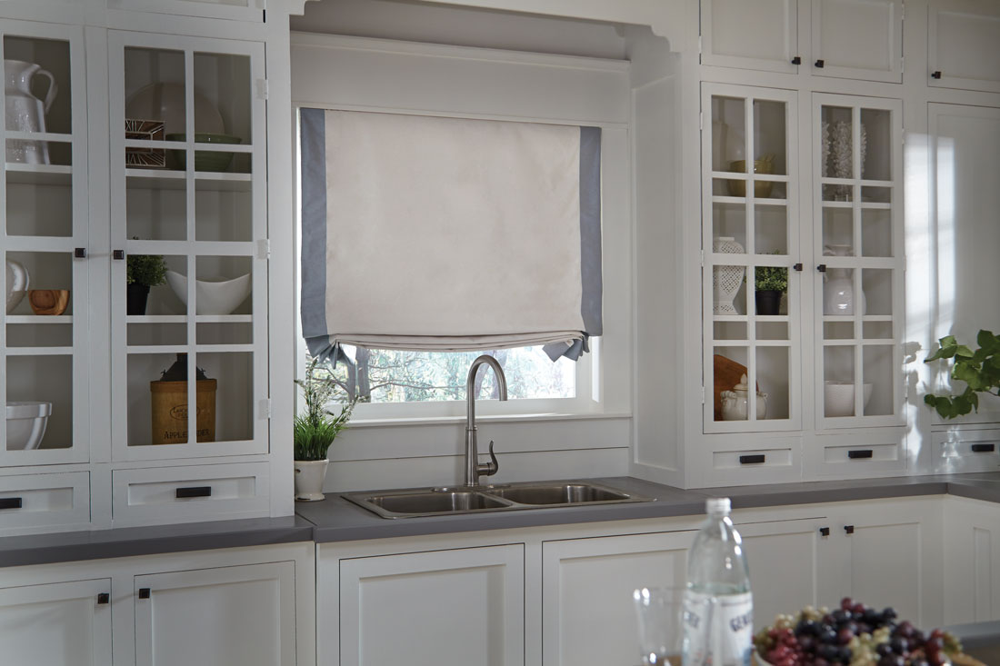 Tan Interior Masterpieces® fabric shade with accenting light blue banding on each side in a kitchen behind a sink
