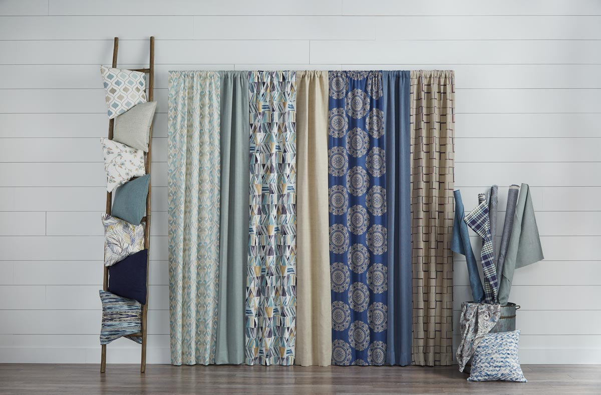several Interior Masterpieces® materials in shades of blue and a stack of custom pillows next to them