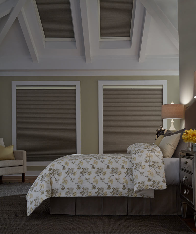 Large tan Parasol® Duo Lucent Cellular Shades and skylights behind a bed with white, yellow, and brown Interior Masterpieces® Custom Bedding