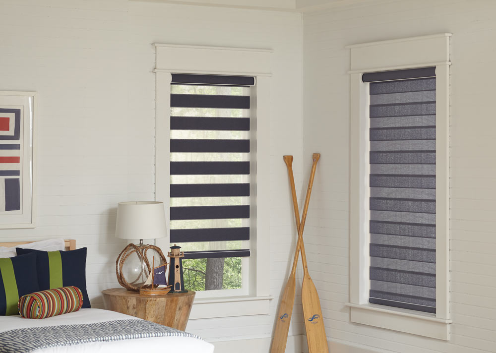Two light gray Allure® Transitional Shades in a bedroom with oars leaning on the wall in between them